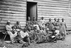 "A group of ""contrabands"" (a term used to describe freed or escaped slaves) in front of a building in Cumberland Landing, Virginia, on May 14, 1862."