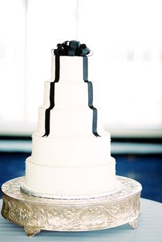 Five tier white wedding cake with black bow