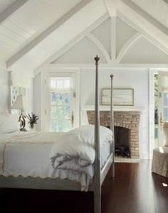 small romantic cottage guest bedroom with fireplace and painted wood ceiling