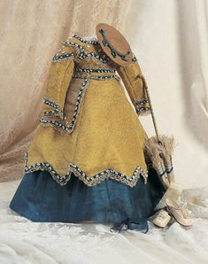 """French Silk Gown with Accessories for Huret Type Poupee    To fit 17"""" (43 cm) poupee. The ensemble includes three piece gown of gold and blue silk with white beadwork and detachable sash; along with metal handled parasol by Farge for Huret having blue and yellow silk striped cover with fringe,Huret style kidskin shoes with tiny heels,straw bonnet and blue kidskin purse. Very good condition,three tines need repair on parasol. French,circa 1865."""