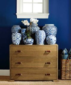 A tiered grouping of antique-style vases gets a blue boost from a denim-colored wall. | Washed Denim (RL1948), Harbor Blues Lifestyle Palette, @ralphlauren Paint at The Home Depot