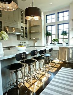 Love this kitchen.  Nice mix of materials, glass cabinets, open shelves, black window frames, area rug, stools. . . .