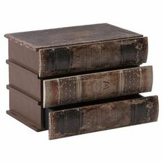 """Stylishly stow photographs, trinkets and accessories in this handsome storage box, showcasing a stacked book silhouette and 3 essential drawers.    Product: Storage boxConstruction Material: Engineered wood and faux leatherColor: BrownFeatures: Three drawersDimensions: 10.5"""" H x 7.5"""" W x 6.75"""" D"""