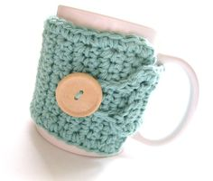 Image: a hand-crocheted coffee cozy with a large wooden button. The cozy is being displayed on a white D-ring mug.