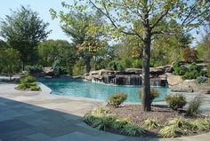 Swimming Pool with Garden Oasis Patio - If one can perfect a natural setting, this is it. The waterfall integrates the pool with its rocky surroundings. Photo courtesy of Creative Master Pools, Inc. http://www.luxurypools.com/builders-designers/creative-master-pools-inc.aspx