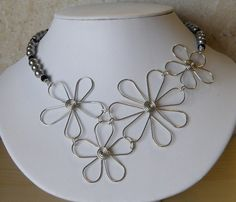 Super fun necklace made with hand-made wire flowers and glass beads. This necklace ships for free and includes matching earrings!! Flowers are made with anti-tarnish silver plated wire, and spacer beads are silver plated. Flowers in the center of the necklace are slightly off-set. Approx. 18 inches.    Ships free on etsy.com