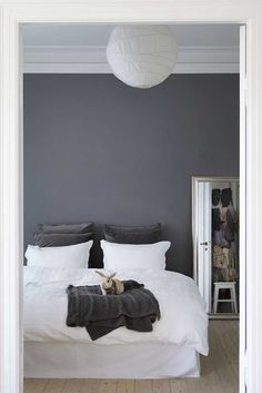 Grey accent wall and white accessories for the bedroom.