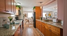Gorgeous galley kitchen with granite counter tops and honey colored cabinets.