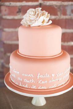 E.E Cumming's round two-tier wedding cake - pink with white writing