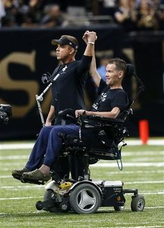 New Orleans Saints head coach Sean Payton, left, leads a cheer with former Saints player Steve Gleason, who suffers from ALS, before an NFL football game against the Atlanta Falcons in New Orleans, Sunday, Sept. 8, 2013. (AP Photo/Bill Haber)