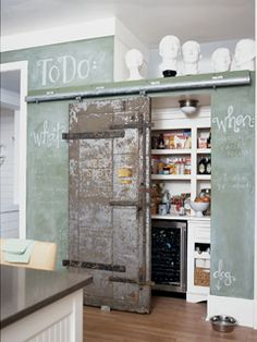 This unique pantry portal was a vintage door from an old New Orleans bank safe and is installed on a sliding track. A chalkboard effect on the walls was achieved by mixing wall paint and unsanded grout.