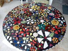 Mosaic-ed table top with wildflowers and black grout.