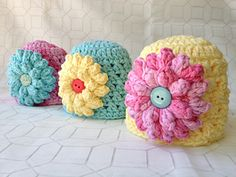 Newborn Beanie free crochet pattern as a Ravelry download. Make multiple flowers in various colors with a snap on the back to coordinate with various outfits.