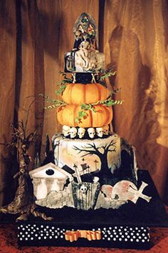 Four tier halloween graveyard cake with a pumpkin cake as the second tier. Beautifully hand painted and decorated with crosses, skulls and hand painted artwork. Topped with a bride and groom corpse wedding cake topper. From www.letthemeatcake.net #wedding #cake #birthday
