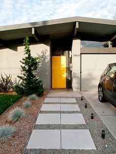 I love the bright yellow door on this Eichler home. A pop of color in the center of a neutral exterior is perfect for these famous modern homes.