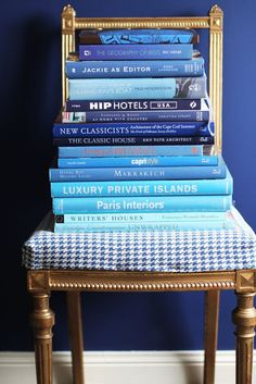 Blue walls, gilt chair with blue and white houndstooth, blue book spines