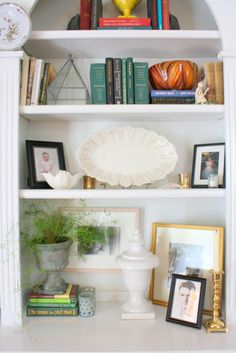Love how these bookshelves are styled. Great mix of books, photos, art, plants and other decorative accessories.