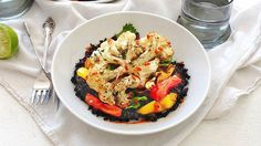 Cauliflower steaks roasted and served with colorful peppers and coconut black rice. You won't believe it.