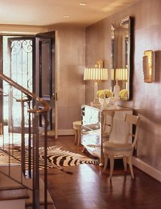 Warm silver leaf wallcovering makes this entry inviting and glamorous.