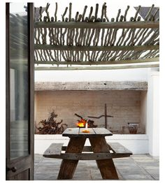 Outdoor fire and twig/branch pergola roof - rustic timber table and benches