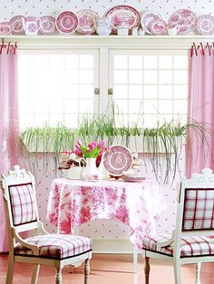 Plates In the Pink: Part shelf, part window treatment, this plate display spans the width of a window with color and style. Mixed plates, platters, teapots, and smaller pitchers combine to make an eye-catching display.