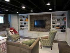 Unfinished basement  with beam ceiling, carpeting and built-in with flat-screen TV