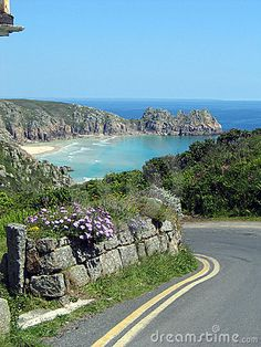 Coastal lane with flowers along a stone wall, overlooking the sea. Blue sky and a cove with cliffs and a beach in the background. Porthcurno, Cornwall, England.