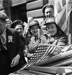 Canadian soldiers and members of the Canadian Women's Army Corps (C.W.A.C.) buying flags to wave in V-E Day celebrations, London, England, 8 May 1945. #vintage #WW2 #1940s #women