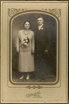 1920-1930s bride and groom.  Her bouquet seems to be attached to the shawl collar of her sweater!