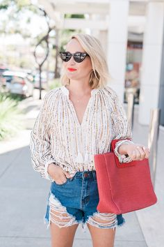 The most amazing Johnny Was sequin top for summer casual chic outfit ideas.  Easy but chic looks for day to night or on summer vacation everywhere. this sequin blouse, denim cut-offs and a bright tote bag are the perfect combo. @thestyleeditrix #summeroutfitideas #weekendoutfits #trendydenim #ootd #vacationoutfit