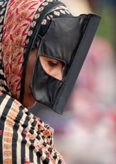 Bedouin woman with mask, Sinaw, Oman.  Bedouin females wear the Omani burqa, or mask, after reaching puberty | © Eric Lafforgue
