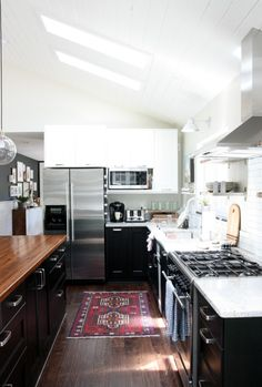 House Tweaking, Dana Miller's Kitchen, Ikea Ramsjö Black Kitchen Cabinets, Red Persian Area Carpet on wood floor | Remodelista