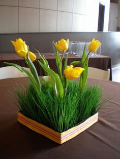 I like this centerpiece of ornamental grass & tulips for Spring. Maybe grow the grass with a hole in the center to place a glass vase, fill the vase with cut tulips, hyacinths, or other Spring-type flowers?