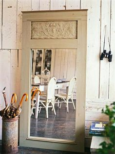 Recycle a door. Use a piece of paintable textured wallcovering for the inset panel above the mirror. Surround the mirror with decorative trim.