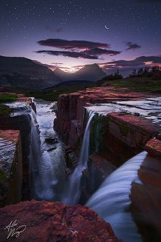 Morning twilight and a rising moon over Glacier National Park's Triple Falls, Montana