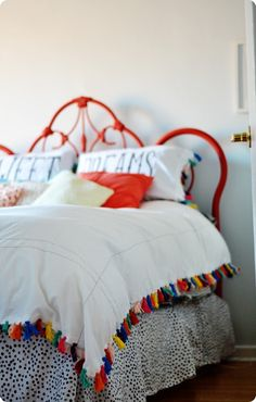 Make your own Anthropologie inspired duvet cover like this colorful tassel trimmed one using two sheets and embroidery floss. This DIY duvet cover is inexpensive to make but packs a serious decorative punch!