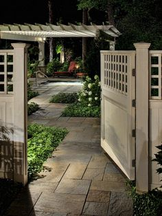 An open, smooth cedar entry gate reveals a pergola garden. Pathway and accent lighting combine to create a romantic evening atmosphere.