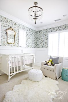 Lovely nursery features aviary wallpaper on top half of wall and wainscoting on bottom half of wall framing gilt ornate mirror over white traditional crib dressed in white and pink crib bedding. Girl's nursery with white beaded glass chandelier over oatmeal linen glider accented with gray pillow and paired with turquoise stool and white Moroccan leather pouf over sheepskin rug layered over beige wall to wall carpeting.