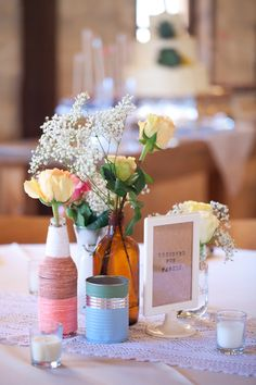 centerpiece with doily, tin can, brown glass vase and bottle wrapped in twine