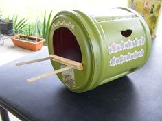 """1 Large Folgers Coffee (Plastic container) – Green Spray Paint – Scissors (to cut openings) – Scrapbook decals – 2 Popsicle sticks – 1 small dowel (cut for perch) = Next Bird Nest home. Mount under patio eve so not to worry about weather elements. I will let you know if it works. It was fun to make and the birds will nest up to 3 times a year – so this will """"hold out"""". I did not glue the lid on – so if it needs to be """"cleaned out"""" after – it will be accessible."""