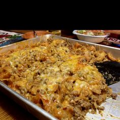 Walking Taco Casserole ... Yum!    Brown 1 1/2 lbs ground beef with about 1/3 of a large onion- chopped  Add a small can of green chilies, 1 can of enchilada sauce, and 2 oz. cream cheese (optional) to the meat  Layer in a casserole dish in the following order: Fritos chips, meat mixture, shredded cheese  Repeat layers once again  Bake at 350° for about 15-20 min or until cheese is bubbly  Top individual dishes with lettuce, salsa, sour cream or your favorite taco topping  ENJOY!