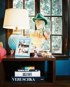 A dandy bust and a blue-glass lamp on a wooden end table