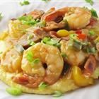 """Old Charleston Style Shrimp and Grits: 1 cup coarsely ground grits 3 cups water 2 tsp salt 2 cups half-and-half 2 lbs uncooked shrimp, peeled & deveined salt to taste 1 pinch cayenne pepper 1 lemon, juiced 1 lb andouille sausage, 1/4"""" slices 5 slices bacon 1 green bell pepper 1 red bell pepper 1 yellow bell pepper 1 cup chopped onion 1 tsp minced garlic 1/4 cup butter 1/4 cup flour 1 cup chicken broth 1 tbsp Worcestershire sauce 1 cup shredded Cheddar cheese"""