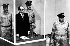 Adolf Eichmann stands in his glass cage, flanked by guards, in the Jerusalem courtroom where he was tried in 1961 for war crimes committed during World War II. After his kidnapping by Israeli Mossad agents in Argentina, Eichmann was tried and convicted of all 15 charges against him including crimes against humanity, and was executed on May 31, 1962. (The horrendous part is what HE did to help Hitler, not his trial.)