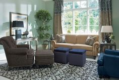 A geometric area rugs brings together a love seat and chair with ottoman in a smaller space with table accents.
