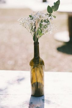 wine bottle centerpiece, photo by Sarah Beth Photography http://ruffledblog.com/intimate-louisiana-wedding #wedding #reception