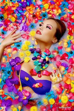 model covered in colorful flower petals lying in water
