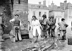 American soldiers stand in the village of Sainte-Marie-du-Mont, which was liberated by paratroopers of the 501st and 506th Regiments of the 101st Airborne.