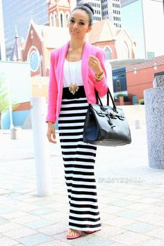 pink blazer with a black and white striped skirt.