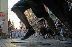 Participants run in front of Dolores Aguirre Ybarra's fighting bulls on the 4th San Fermin Festival bull run,